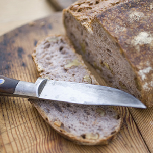 A loaf of rustic artisan bread on a wooden cutting board with a knife.